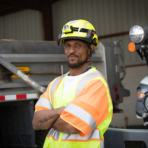 Workman standing with hat, safety gear, arms crossed.