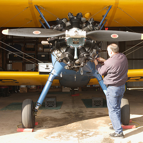 A man working on a propeller on a yellow airplane.