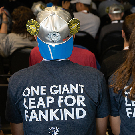 a man shows the back of his t-shirt: one giant leap for mankind