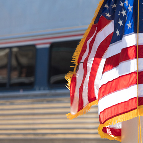 American flag in front of an amtrak
